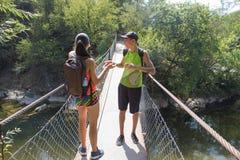 Trekking совместно Активные hikers Путешественники путешествуют на искусственной проезжей части висячего моста Стоковая Фотография RF