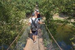 Trekking совместно Активные hikers Путешественники путешествуют на искусственной проезжей части висячего моста Стоковое Изображение RF