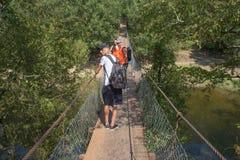 Trekking совместно Активные hikers Путешественники путешествуют на искусственной проезжей части висячего моста Стоковое фото RF