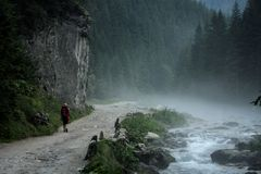 Trekking. Woman amongst mountains alongside mountain stream Stock Photo