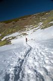 Trekking alone on snow path Royalty Free Stock Images