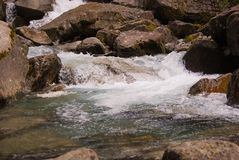 Stream of a mountain river rises from a perennial glacier stock photography