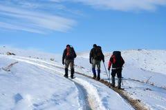 Trekking auf schneebedecktem Pfad an einem sonnigen Wintertag Lizenzfreies Stockfoto