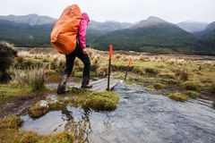 Trekking in bad weather. Across flooded river stock photos