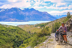 Trekking with bicycle in southern Patagonia. Cyclist pushing his bicycle uphill on a narrow rocky path at the end of the Carretera Austral, leading to the border royalty free stock images