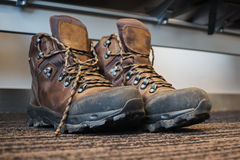 Trekking boots under the seat at the airport Royalty Free Stock Image