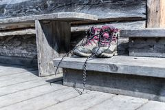Trekking boots on the veranda of an alpine hut. Summer holidays in the mountains. Close up picture of hiking boots on a rustic wooden veranda of an alpine hut royalty free stock images