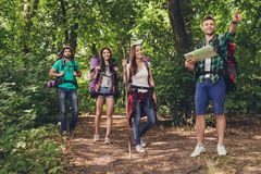 Trekking, camping and wild life concept. Four best friends are h. Iking in the spring woods, the guy is showing the direction, lady is checking it on a map, all stock images