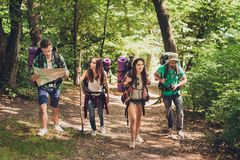 Trekking, camping and wild life concept. Four best friends are hiking in the spring woods, the guy is checking the route on a map,. All are excited and joyful stock photos
