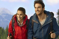 Trekking couple climbing uphill smiling. Stock Photos