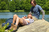 Trekking couple resting at lakeside Stock Image