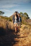 Trekking de couples de randonneur ensemble dans la campagne Photos stock