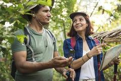 Trekking de couples ensemble dans une forêt Images stock