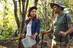Trekking de couples ensemble dans une forêt Photographie stock libre de droits