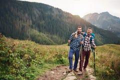 Trekking de sourire d'amis ensemble dans les collines Image libre de droits