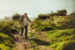 Trekking dell'uomo su una collina facendo uso dell'escursione dei pali immagini stock