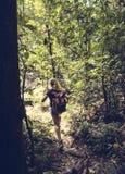 Trekking della donna nella foresta immagini stock