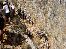 Trekking di anni dell'adolescenza giù una montagna Fotografie Stock