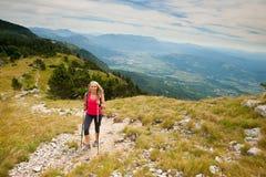 Trekking - donna che fa un'escursione in montagne un giorno calmo del sumer Immagini Stock