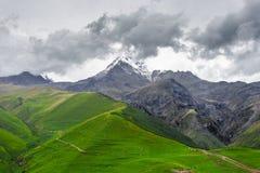 Trekking em montanhas de Cáucaso (Geórgia) - vista da montagem Kazbek coberto com as nuvens Fotos de Stock