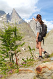 Trekking girl on high mountain trail pointing at peak Stock Photo