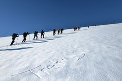 Trekking group. A group of hikers trekking up a snowy hill Stock Image