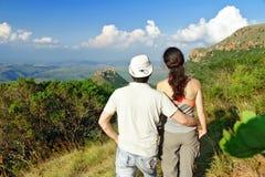 Trekking heureux de couples en montagnes, augmentant des touristes Photographie stock