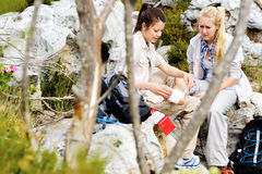 Trekking injury. A women has sprained her ankle while hiking, her friend uses the first aid kit to tend to the injury stock photos