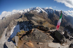 Trekking in the Italian Alps: italian flag over a top in the Alps Royalty Free Stock Photo