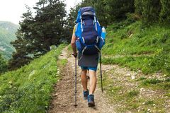 Trekking. Men with backpacks on mountain trek. Hiking trail. Path with two tourist through forest. Sport tourism. Hikers in way stock images