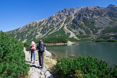 Trekking in Mountains. Couple trekking by the side of mountain pond in Tatra Mountains, Poland stock photos
