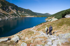 Trekking in mountains. Couple trekking by the side of mountain pond in Tatra Mountains, Poland stock image