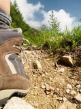 Trekking on the mountains. An unusual composition of a trekking boot on a mountain path with blue sky in the background stock photography