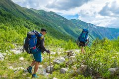 Trekking in mountains. Friends hike in mountain trail stock photos