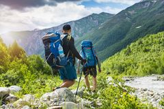 Trekking in mountains. Mountain hiking. Tourists with backpacks hike on rocky way near river. Wild nature with beautiful views. royalty free stock image