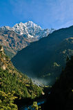 Trekking the Nepal Himalayas. Landscape shot overviewing a valley covered in mist. in the background you can see the himalayas Royalty Free Stock Photos