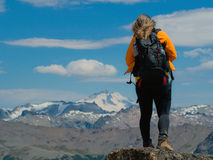 Trekking in Patagonia. Woman with backpack walks on the rocks of Cerro Catedral, with snowy Mount Tronador in the background - Bariloche - Patagonia - Argentina Royalty Free Stock Photo
