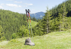 Trekking poles and trekking shoes on background of forested moun Stock Photos