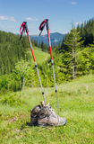 Trekking poles and trekking shoes on background of forested moun Royalty Free Stock Images