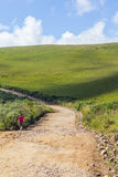 Trekking on the Road. Girl trekking on the dirt road in Cambara do Sul, Rio Grande do Sul, Brazil Stock Photo