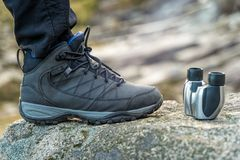 Trekking shoe and binocular closeup on a rock in the mountains during a sunny day, blurred background stock image