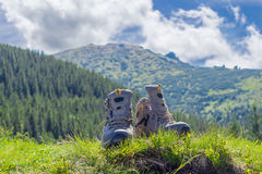 Trekking shoes on blurred background of forested mountains and s Stock Photo
