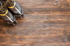 Trekking shoes with crampons on dark wooden background, top view. Climbing equipment. Travel concept Stock Photos