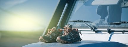 Trekking shoes are drying on a dirty 4wd car bonnet. Adventure mood stock image