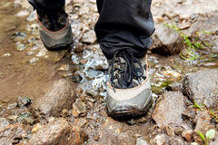 Trekking shoes. Hiking shoes on hiker outdoors walking crossing river creek. Woman on hike trekking in nature. Closeup of female hiking shoes in action. Trekking Stock Images