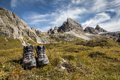 Trekking shoes outdoor. Trekking shoes boots on grass in front of stunning mountain scenery and blue skies clear weather. The mountain in the background is Monte stock photography