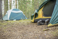 Trekking shoes are in the tent. In a forest stock photography