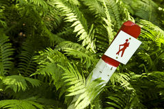 Trekking signpost. Red and white trekking signpost surrounded by ferns Stock Images