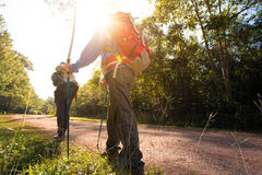 Trekking. Two woman trekking along the forest pathway with trekking pole in morning sunlight Royalty Free Stock Photography