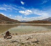 Trekking wandelingslaarzen bij bergmeer in Himalayagebergte Stock Fotografie